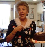 An older white woman with short grey-blond hair and wearing a black sweater with snowmen on it and a lacey collar holds a chocloate cake in one had and oints to herself with the other